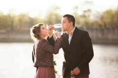 Wedding couple, groom and dress posing near river with a glass at sunset Stock Images