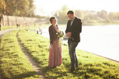 Wedding couple, groom and dress posing near river with a glass at sunset Royalty Free Stock Photography
