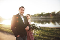 Wedding couple, groom and dress posing near river with a glass at sunset Royalty Free Stock Photos