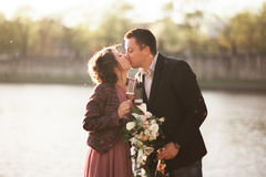 Wedding couple, groom and dress posing near river with a glass at sunset Royalty Free Stock Photo