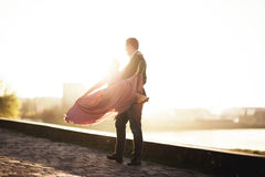 Wedding couple, groom and dress posing near river with a glass at sunset Stock Photos