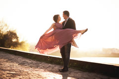 Wedding couple, groom and dress posing near river with a glass at sunset Stock Photo