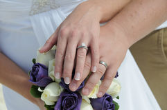 Wedding couple hands on purple flowers Royalty Free Stock Photography