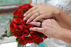Wedding couple hands on red flowers Stock Photos