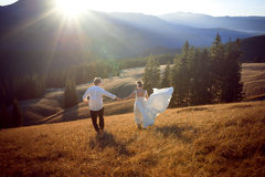 Wedding couple having fun in the mountains. Honeymoon Stock Images