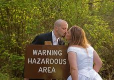 Wedding Couple Hazardous Area Sign. This is a humorous concept photo of a couple in their wedding attire kissing next to a Warning Hazardous Area sign Royalty Free Stock Image