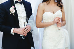 Wedding couple hold glasses with champagne in their arms Stock Image