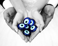 Wedding Couple Holding Evil Eyes in Their Hands. Evel Eyes are in hands Stock Photography