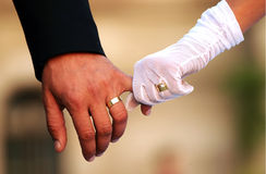 Wedding couple holding hands. Shot of the hands of a wedding couple. Both wedding rings are visible, plus the engagement ring Stock Photos