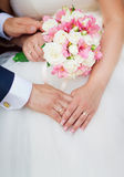 Wedding couple holding hands with a bouquet of flowers Royalty Free Stock Photos