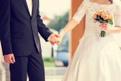 Wedding couple holding hands with flower holding.  Royalty Free Stock Photo