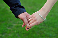 Wedding couple holding hands on grass background Royalty Free Stock Images