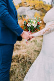 Wedding couple holding hands outdoors. Groom in blue suit and bride white dressed with floral bouquet.  Stock Images