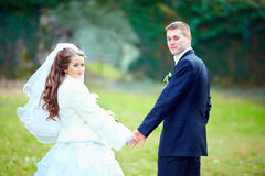 Wedding couple holding hands in park Stock Photo