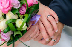 Wedding couple holding hands with their rings. Bride and groom holding their hands together over the bridal bouquet and showing their wedding rings Stock Image