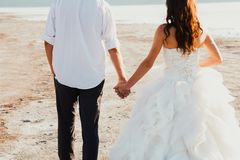 Wedding couple is holding hands and walking away on the sea beach. Sunny summer photo. Bride with hair down in off shoulder dress stock photo