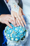 Wedding couple holding hands on wedding bouquet Stock Images