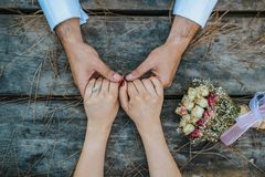 Wedding couple holding hands on wooden table with bouquet. stock photos