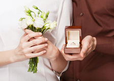 Wedding couple holding ring box and a bouquet of flowers Stock Photos