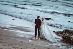 Wedding couple holds each other hands walking along the beach near ocean waves in the evening light. Attractive wedding couple holds each other hands walking stock images