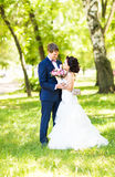 Wedding couple hugging, the bride holding a bouquet of flowers,  groom embracing her Stock Photography