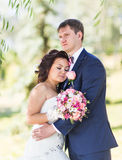 Wedding couple hugging, the bride holding a bouquet of flowers,  groom embracing her Royalty Free Stock Photo