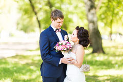 Wedding couple hugging, the bride holding a bouquet of flowers,  groom embracing her Royalty Free Stock Photos
