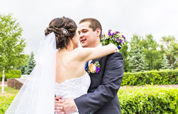 Wedding couple hugging, the bride holding a bouquet of flowers,  groom embracing her Stock Images