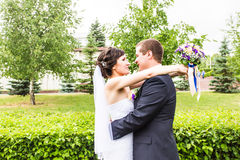 Wedding couple hugging, the bride holding a bouquet of flowers,  groom embracing her Stock Image