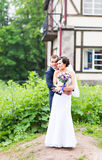 Wedding couple hugging, the bride holding a bouquet of flowers,  groom embracing her Stock Photos