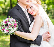 Wedding couple hugging,  bride holding a bouquet of flowers, the groom embracing her Stock Images