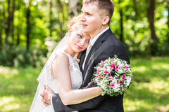 Wedding couple hugging,  bride holding a bouquet of flowers, the groom embracing her Stock Photos