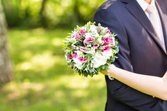 Wedding couple hugging,  bride holding a bouquet of flowers, the groom embracing her Stock Photo