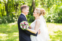 Wedding couple hugging,  bride holding a bouquet of flowers, the groom embracing her Royalty Free Stock Image
