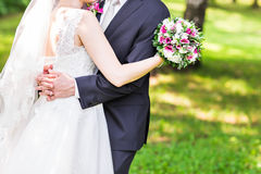 Wedding couple hugging,  bride holding a bouquet of flowers, the groom embracing her Royalty Free Stock Photos