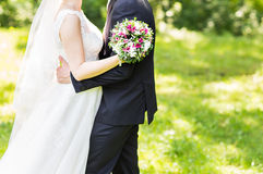 Wedding couple hugging,  bride holding a bouquet of flowers, the groom embracing her Stock Photography