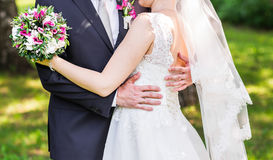 Wedding couple hugging,  bride holding a bouquet of flowers, the groom embracing her Royalty Free Stock Photo