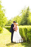Wedding couple hugging, the bride holding a bouquet of flowers in her hand Stock Photo