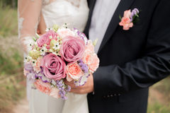 Wedding couple hugging, the bride holding a bouquet of flowers in her hand, the groom embracing. Her Stock Images