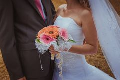 Wedding couple hugging, the bride holding a bouquet of flowers in her hand, the groom embracing her Royalty Free Stock Images