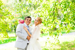 Wedding couple hugging, the bride holding a bouquet of flowers in her hand, the groom embracing her Stock Photos