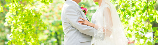Wedding couple hugging, the bride holding a bouquet of flowers in her hand, the groom embracing her Royalty Free Stock Photography