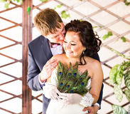 Wedding couple hugging, bride holding fan of peacock feathers, the groom embracing her Royalty Free Stock Images
