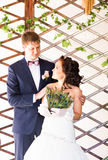 Wedding couple hugging, bride holding fan of peacock feathers, the groom embracing her Stock Photos