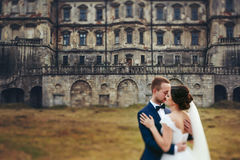 Wedding couple hugs standing on the bakcyard of an old ruined ca. Stle Royalty Free Stock Photo