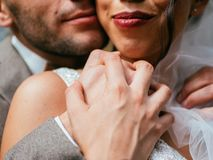 Wedding couple indoors is hugging each other. Beautiful model girl in white dress. Man in suit. Beauty bride with groom. stock photos