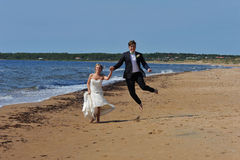 Wedding Couple jumping on the Beach. A Young wedding couple running along the beach by the sea on their wedding day and the groom is jumping high Royalty Free Stock Photo
