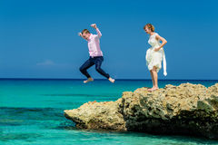 A wedding couple jumping into the ocean Stock Images
