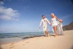 Wedding couple just married holds hands and walking at beach. Wedding couple just married holds hands and walking at the beach, Bali. Successful married couple Royalty Free Stock Photo