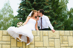 Wedding couple kiss and dangle feet. Tenderness loving. Love people Royalty Free Stock Photography